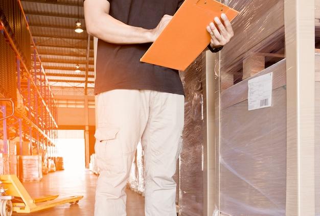 De jonge mens schrijft op klembord met inventaris het product in pakhuis.