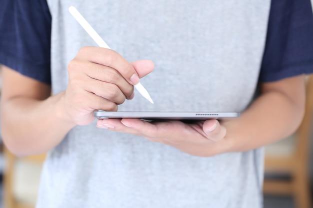De jonge mens schrijft op tablet door wit potlood