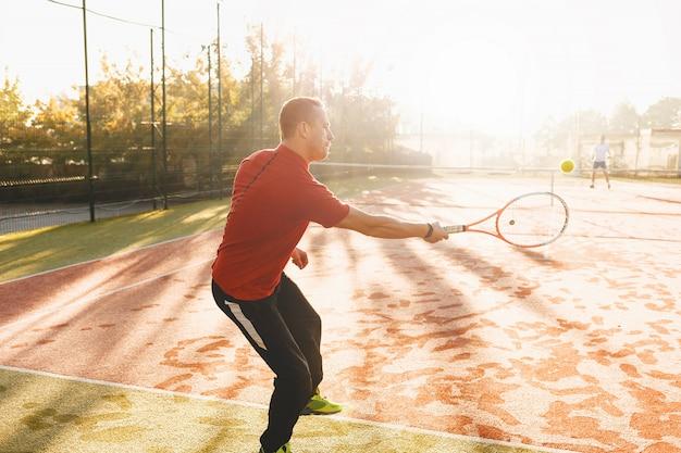 De jonge mens speelt tennis op verse zonnige ochtend