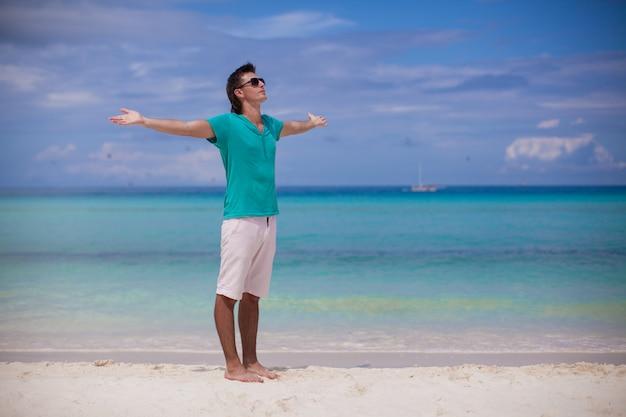 De jonge mens spreidde zijn wapens uit die zich op wit zandig strand bevinden
