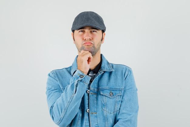 De jonge mens steunt kin op hand in glb, t-shirt, jasje en kijkt peinzend. vooraanzicht.