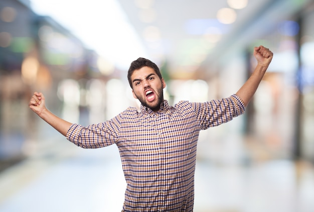 De jonge mens toont woede met armen verbreed.