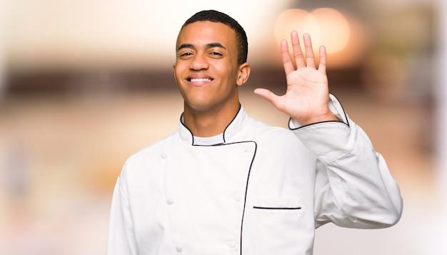 De jonge mens van de afro amerikaanse chef-kok groeten met hand met gelukkige uitdrukking unfocused achtergrond