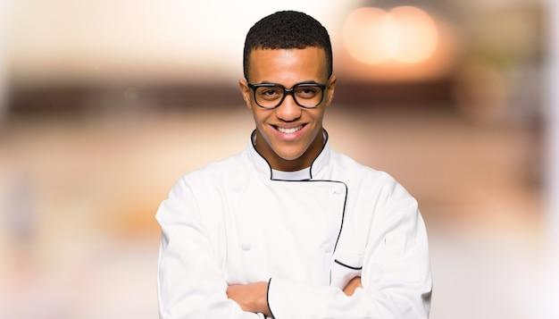 De jonge mens van de afro amerikaanse chef-kok met glazen en gelukkig unfocused achtergrond