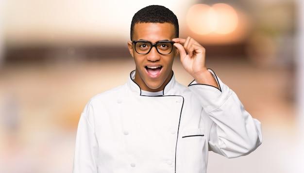 De jonge mens van de afro amerikaanse chef-kok met glazen en verrast unfocused achtergrond