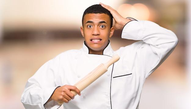 De jonge mens van de afro amerikaanse chef-kok neemt handen op hoofd omdat heeft migraine op ongericht achtergrond