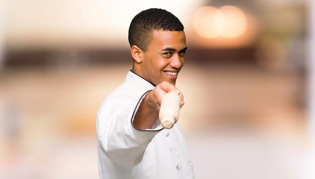 De jonge mens van de afro amerikaanse chef-kok richt vinger op u met een zekere uitdrukking unfocused achtergrond