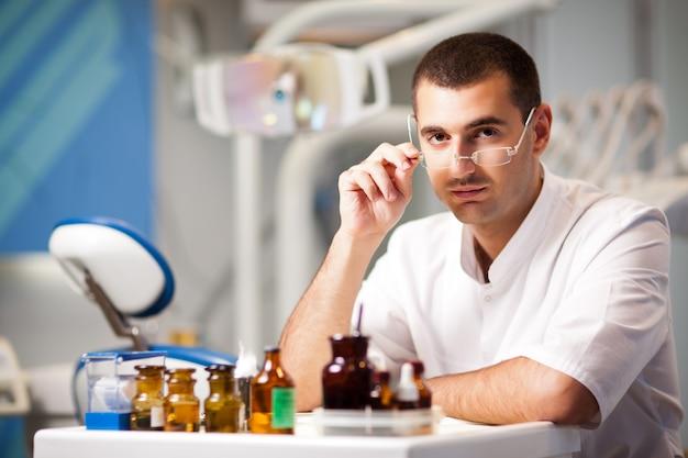 De jonge mens van de artsentandarts in eenvormige zitting dichtbij tandstoel in tandbureau in kliniek met materiaal bij achtergrond