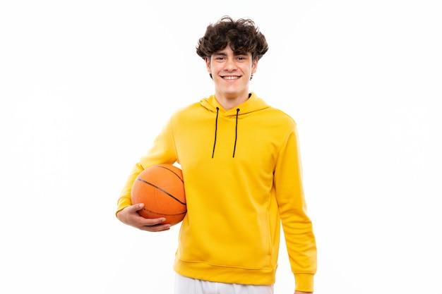 De jonge mens van de basketbalspeler over geïsoleerde witte muur die heel glimlacht
