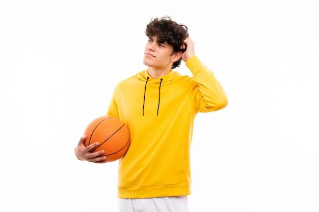 De jonge mens van de basketbalspeler over geïsoleerde witte muur die twijfels hebben en met verwarren gezichtsuitdrukking
