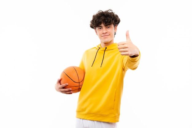 De jonge mens van de basketbalspeler over geïsoleerde witte muur met omhoog duimen omdat iets goeds is gebeurd