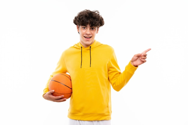 De jonge mens van de basketbalspeler over geïsoleerde witte muur verrast en richtende vinger aan de kant