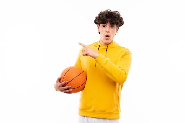De jonge mens van de basketbalspeler over geïsoleerde witte verrast muur en het richten van kant