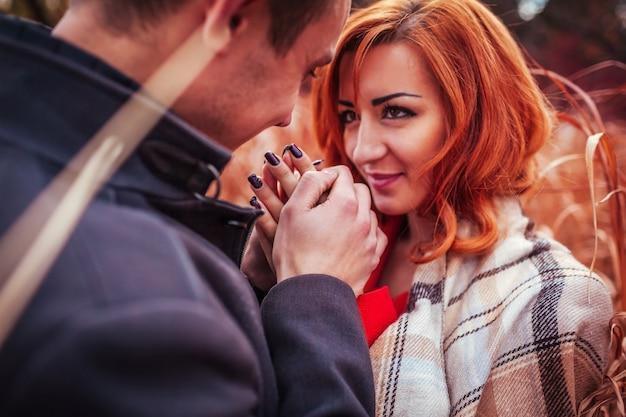 De jonge mens verwarmt de handen van zijn vriendin in de herfstbos
