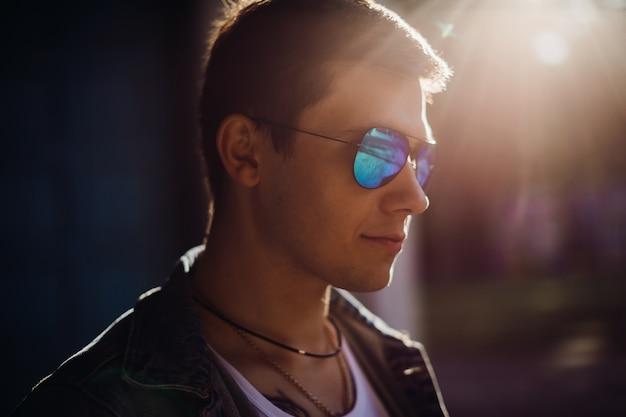 De jonge mens zet op zonnebril die zich buiten bevinden