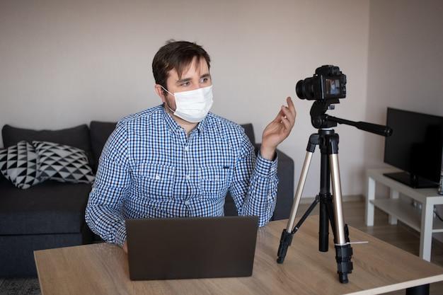 De jonge mensenblogger die beschermend gezichtsmasker dragen neemt video op videocamera op. mannelijke blogger die over de pandemie van het coronavirus streamt. blijf thuis voor zelfquarantaine op afstand