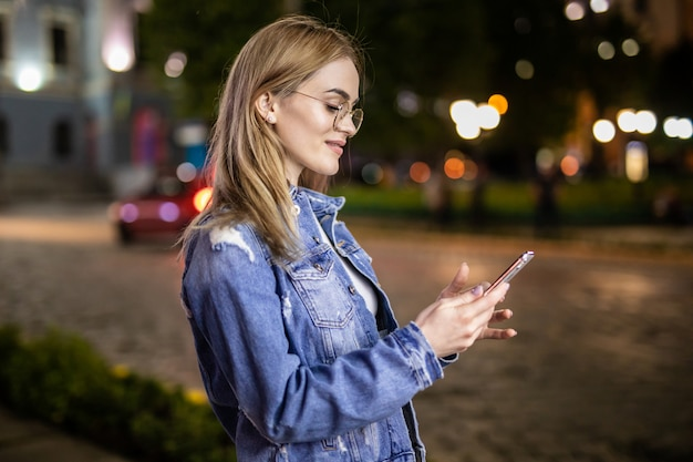 De jonge mobiele telefoon van het vrouwengebruik in stad bij nacht