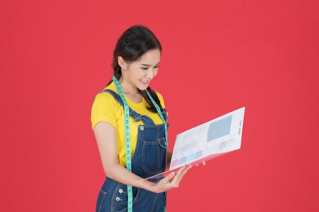 De jonge modeontwerper presenteert de stofstalen in een goed humeur aan de klanten. ze heeft een meetlint om haar nek, klaar om de jurk op een rode achtergrond te knippen.