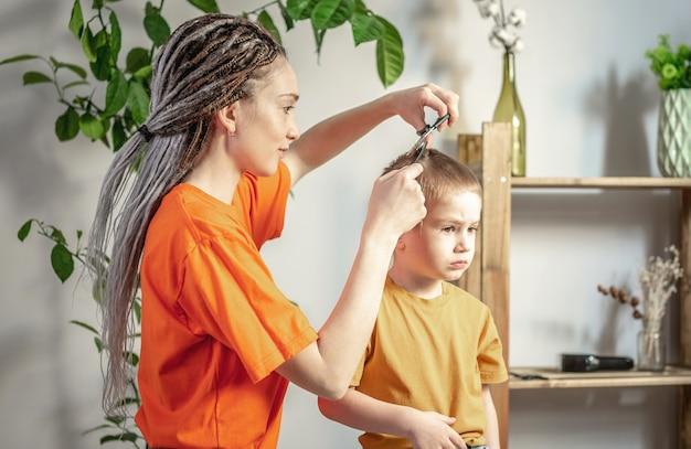 De jonge moderne vrouwenkapper knipt het haar van een kleine jongen met een schaar