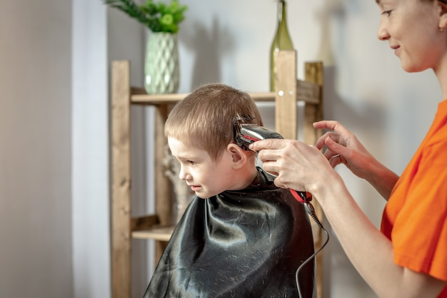 De jonge moderne vrouwenkapper knipt het haar van een kleine jongen met een tondeuse