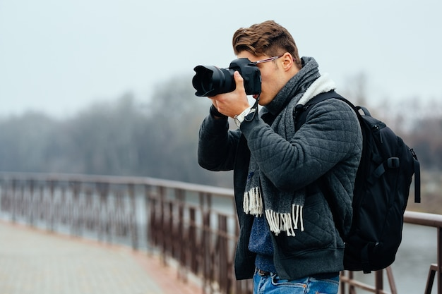 De jonge modieuze fotograaf houdt professionele camera, die foto's neemt.
