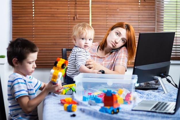 De jonge moeder bedrijfsvrouwenouder onderbreekt door haar jonge geitjeszonen terwijl het spreken op de telefoon en het werken in het huis