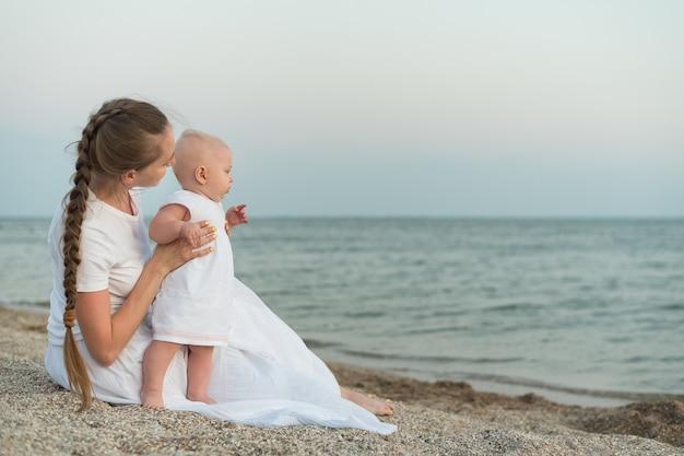 De jonge moeder en de baby rusten op strand. mooie moeder bedrijf baby op zee