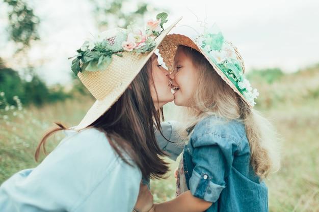 De jonge moeder en dochter met hoeden op groen gras