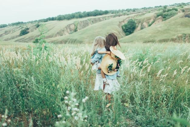 De jonge moeder en dochter op groen gras ruimte