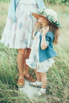 De jonge moeder en dochter op groen gras