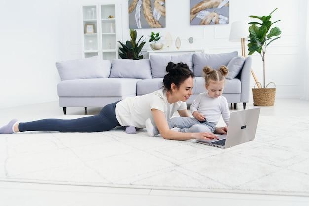 De jonge moeder en haar aanbiddelijke dochter gebruiken laptop terwijl het liggen op de vloer.