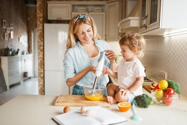 De jonge moeder en haar dochter kloppen de ingrediënten voor cake met een blender in een kom.