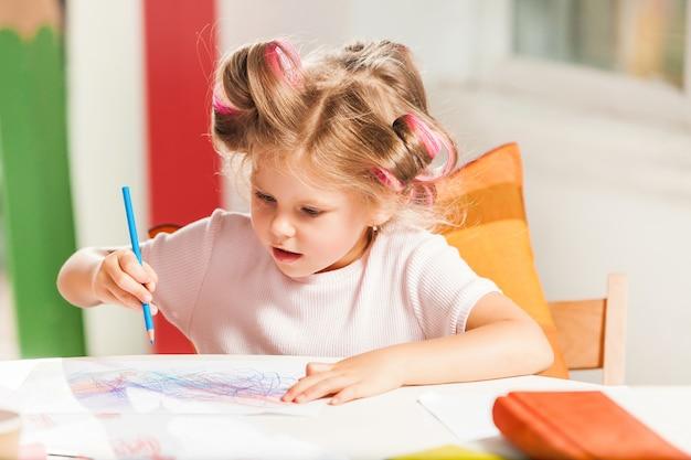 De jonge moeder en haar dochtertje tekenen met potloden thuis