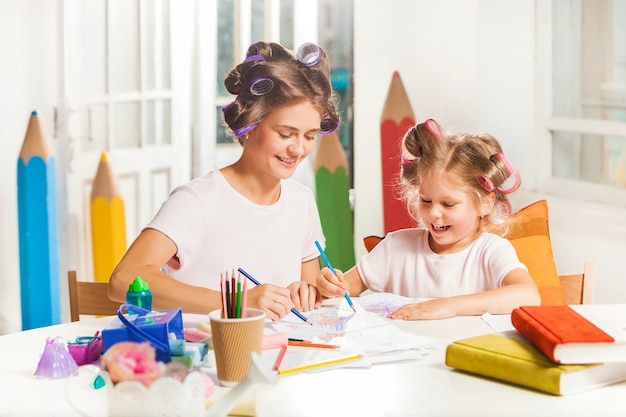 De jonge moeder en haar dochtertje tekenen thuis met potloden