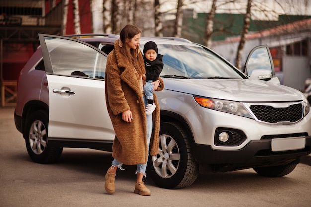 De jonge moeder en het kind bevinden zich dichtbij zij suv auto. rijden veiligheidsconcept.