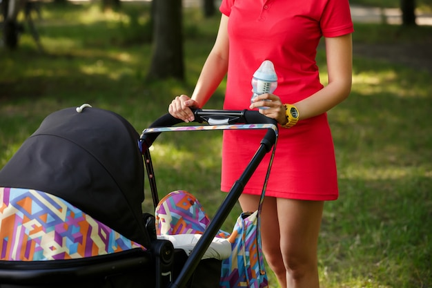 De jonge moeder gaat de baby voeden met een fles babyvoeding en -drank