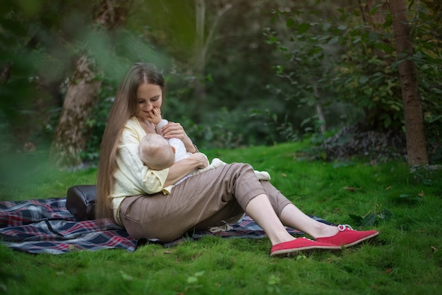 De jonge moeder geeft haar pasgeboren borst