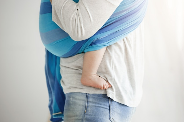 De jonge moeder omhelst teder haar zoon