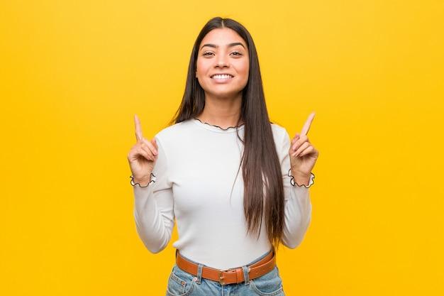 De jonge mooie arabische vrouw wijst met beide voor vingers op die een lege ruimte tonen.