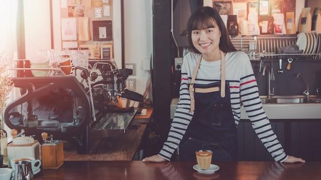 De jonge mooie aziatische barista van de vrouwenbarrière draagt blauwe schort