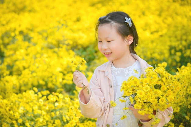 De jonge mooie aziatische de holdingsbloem en de glimlach van het meisjeskind op geel chrysanthemumgebied.