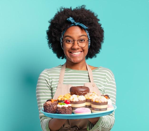 De jonge mooie bakker van de afrovrouw met cakes