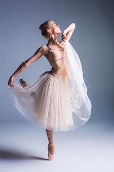 De jonge mooie ballerina dansen op een studio grijze achtergrond