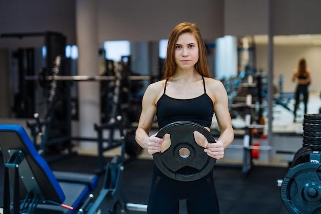 De jonge mooie bodybuilder van de meisjesatleet doet oefeningen in de moderne gymnastiek.