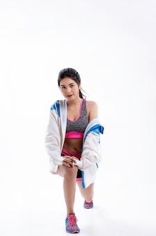 De jonge mooie dame die sportwear draagt, met de voeten uit elkaar, gaat op één knie naar beneden, rekt het lichaam uit voor het sporten, met een gelukkig gevoel