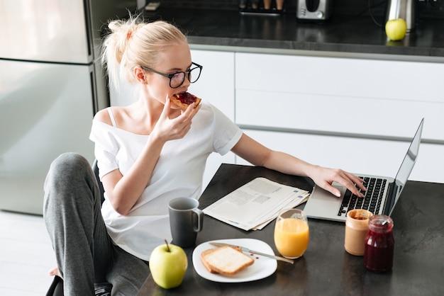 De jonge mooie dame heeft ontbijt en het gebruiken van laptop computer in keuken