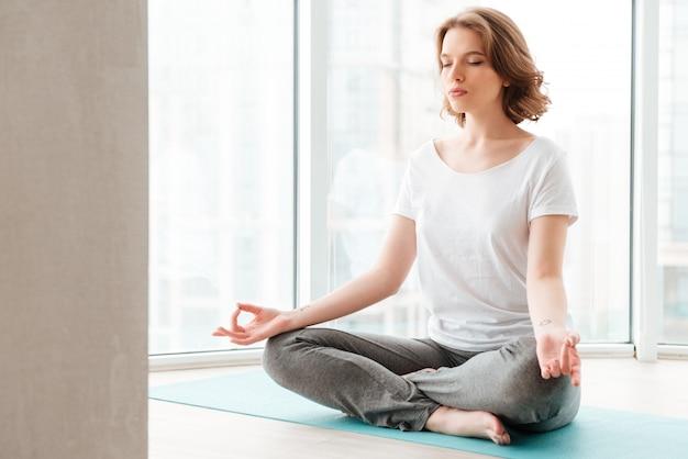 De jonge mooie damezitting dichtbij venster maakt yogaoefeningen.