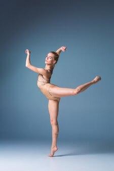 De jonge mooie danseres in moderne stijl die zich voordeed op een studio grijze achtergrond