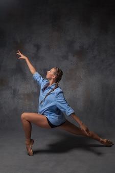 De jonge mooie danseres in moderne stijl in een blauw shirt poseren op een studio grijze achtergrond