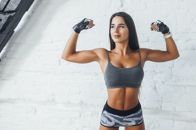 De jonge mooie donkerbruine vrouw toont musculs in de zoldergymnastiek
